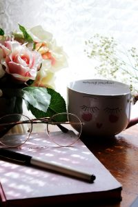 Desk with cup of tea, journal, roses and sun shining through